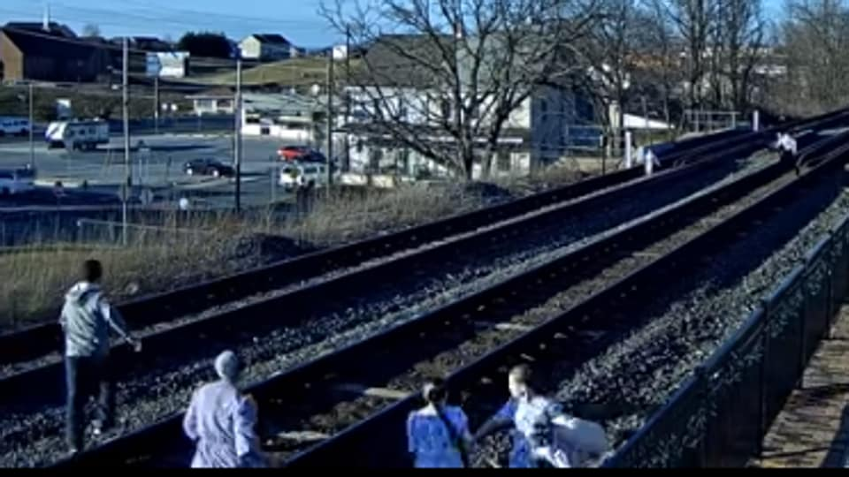 Image shows the members of the family rushing off the tracks.