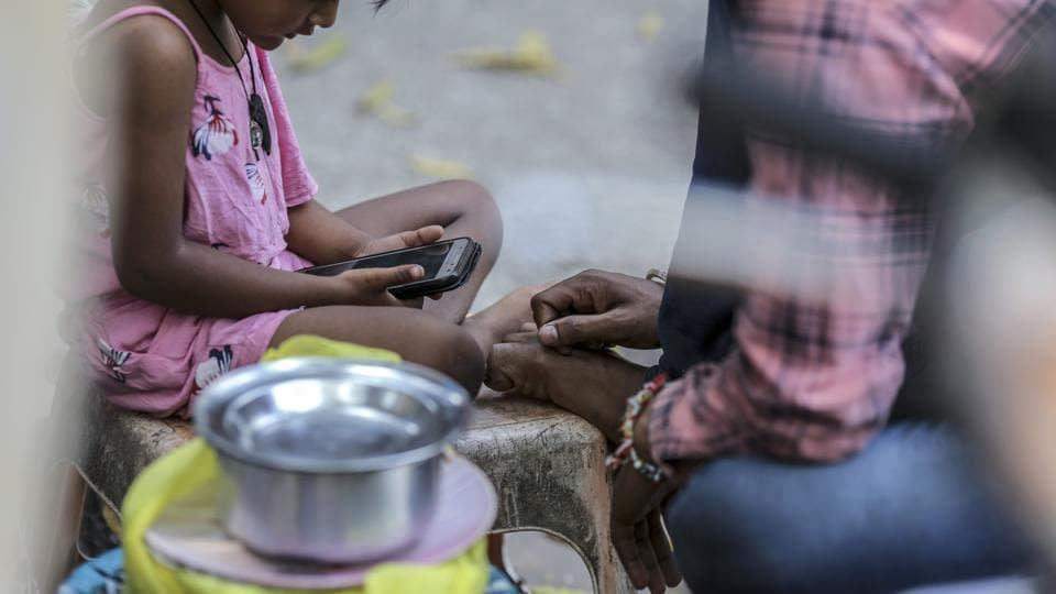 A child uses a smartphone while sitting on the street in Mumbai, India.