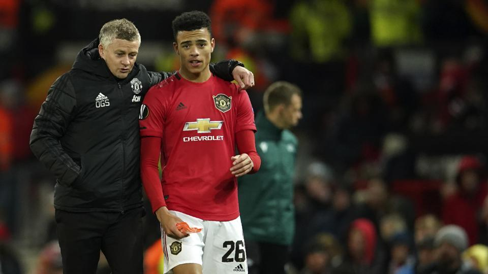 Manchester United's manager Ole Gunnar Solskjaer, left, and Manchester United's Mason Greenwood walk on the pitch.