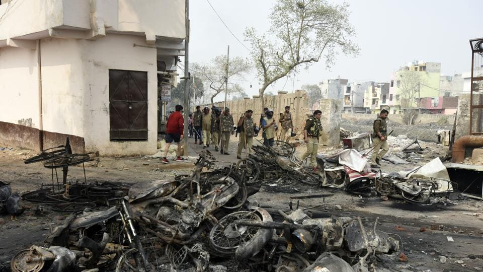 Police and paramilitary personnel on patrol pass burnt vehicles as they make their presence known, after clashes between opposing groups over the Citizenship Amendment Act (CAA) at Karawal Nagar in New Delhi.