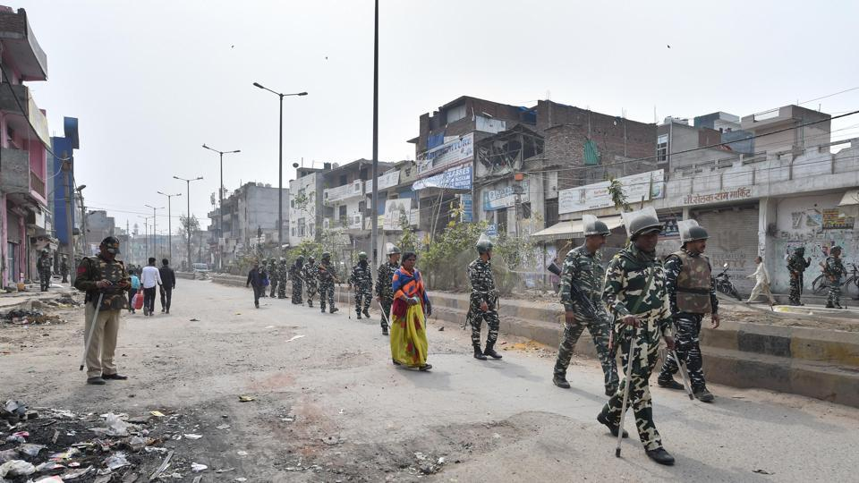 A woman walks along security personnel patrolling a street, at Khajuri Khas area of northeast Delhi on Friday.