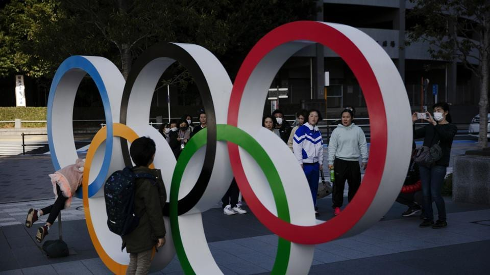People wait in line to take pictures with the Olympic rings near the New National Stadium in Tokyo