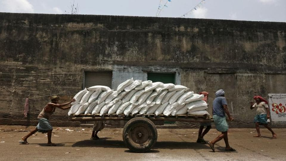 Labourers push a handcart loaded with sacks of sugar at a wholesale market in Kolkata. The latest statistics show that the current economic slowdown has been more severe than what was shown by earlier statistics.