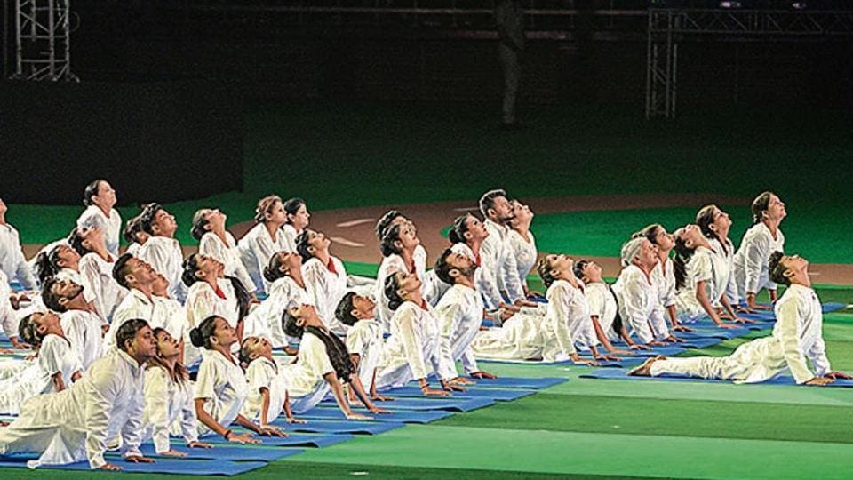 Participants demonstrate asanas during a Fit India programme.