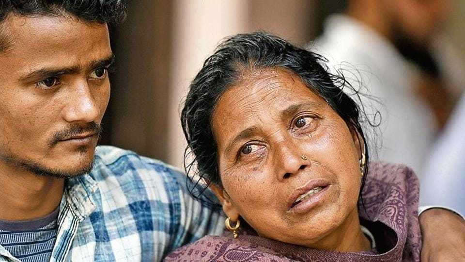 Zajima from Mustafabad, waits for her son's body Monis 22, who was killed during riot, outside GTB hospital mortuary, in New Delhi.
