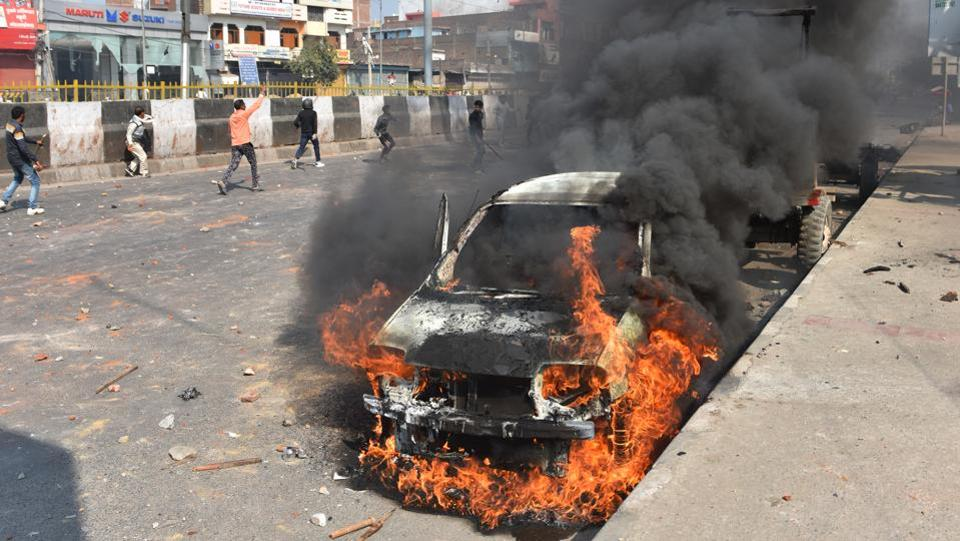 A car is set on fire as protesters rage ahead in the background at Bhajanpura on  February 24. (Sanchit Khanna / HT Photo)