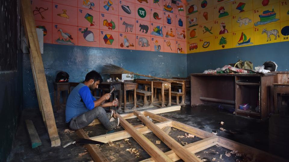 A carpenter works inside the DRP convent school that was damaged in the violence at Shiv Vihar on  March 2. (Sanchit Khanna / HT Photo)