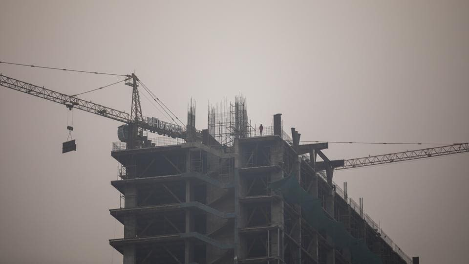 Cranes operate at a Bhutani Group property development in Noida.