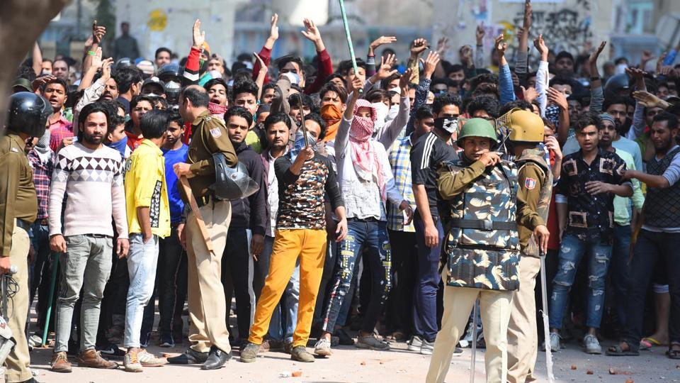 Police personnel stand guard as agitated protesters are seen with weapons at Jaffarabad on February 24.  (Raj K Raj / HT Photo)