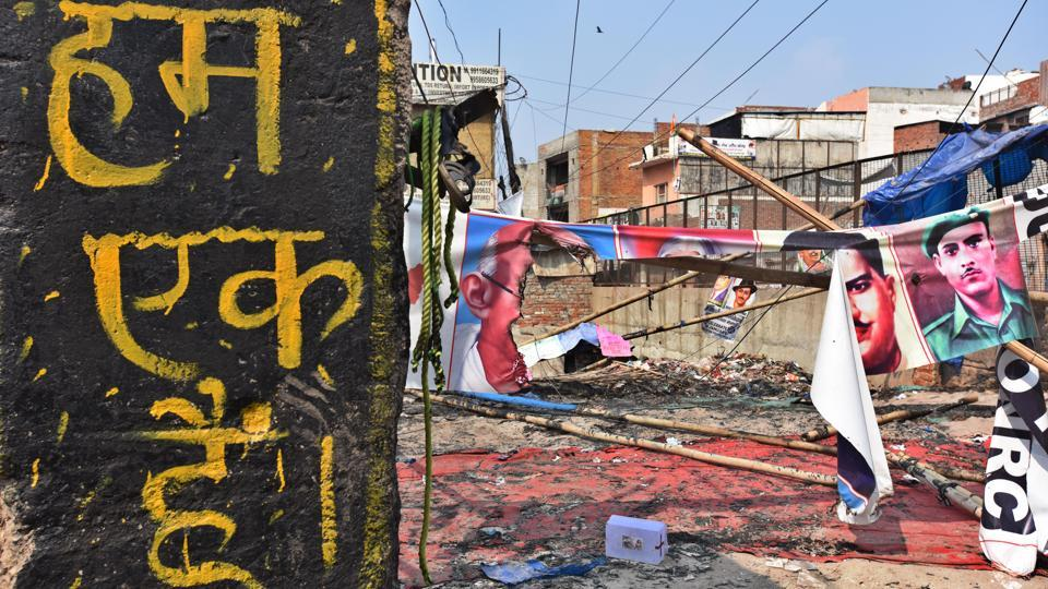 "A slogan reads ""We are one"" as banners bearing the faces of India's freedom fighters are seen damaged in the background following the clashes  at Mustafabad on  February 26. (Raj K Raj / HT Photo)"