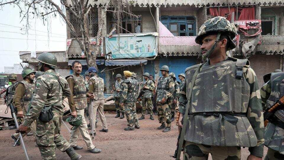 Police stand guard in a riot affected area following clashes in northeast part Delhi