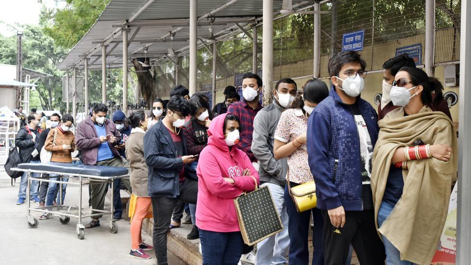 People wearing protective masks stand in a queue near novel coronavirus facilitation centre at Ram Manohar Lohia (RML) Hospital in Delhi on Thursday.
