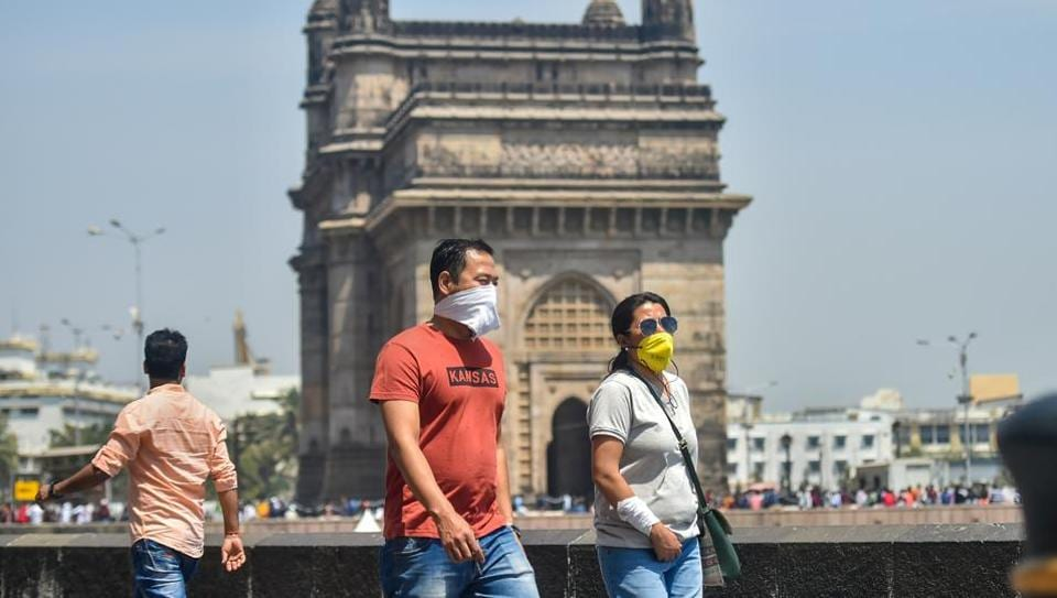 Tourists wear protective masks in view of coronavirus pandemic at Gateway of India in Mumbai.