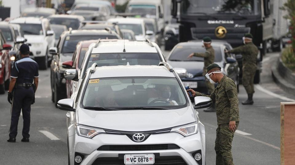 Army troopers use a thermal scanner to check the temperatures of people entering the metropolis at a checkpoint on the outskirts of Quezon city, Philippines.