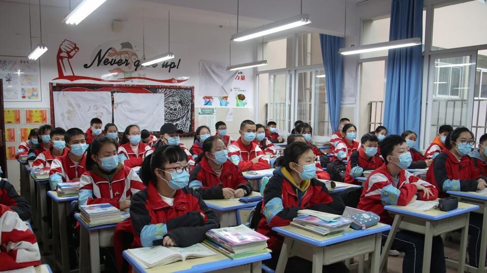 Junior high students wearing face masks attend a class on their first day of returning to school following an outbreak of the novel coronavirus, in Guiyang, Guizhou province, China.
