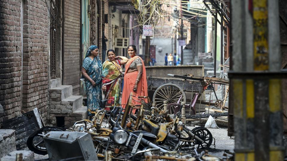 Women stand beside charred remains of vehicles and vandalised properties at Shiv Vihar in Northeast Delhi.