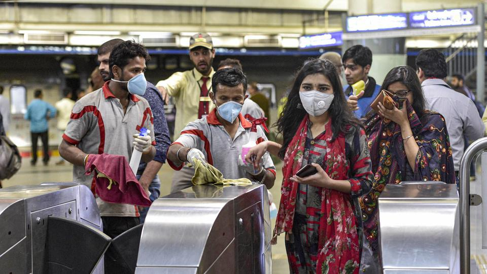 Workers clean entry gates at Rajeev Chowk metro station in the wake of novel coronavirus (COVID-19) outbreak in New Delhi.