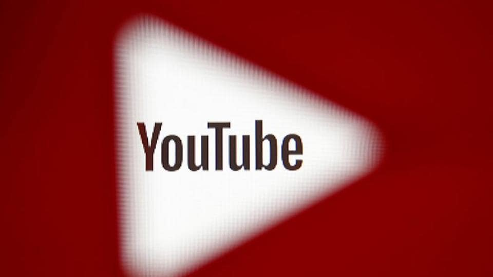 A 3D-printed YouTube icon is seen in front of a displayed YouTube logo in this illustration.