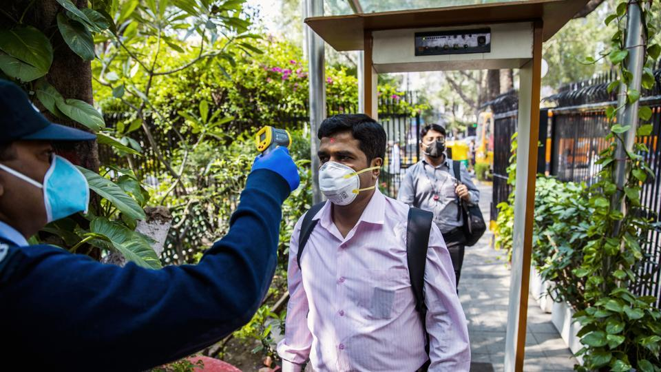 An office worker wearing a protective mask is screened with an infrared thermometer as he enters a building in New Delhi.