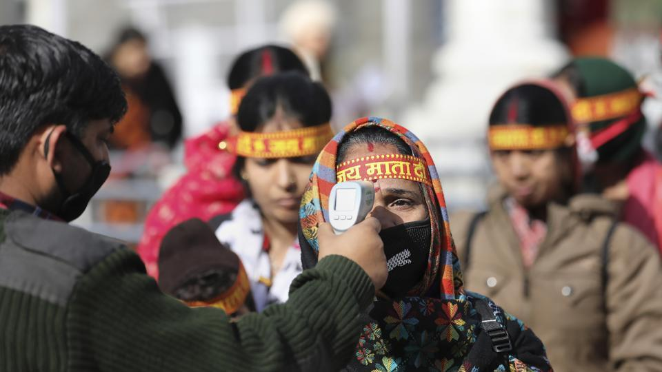 An official uses a thermal screening device on devotees as coronavirus pandemic spreads in India, at Vaishno Devi on Friday.