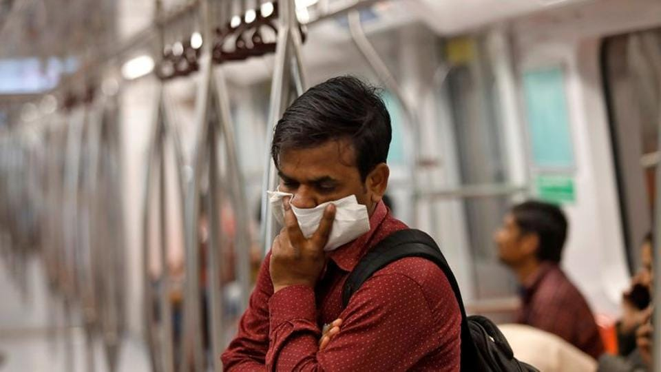 A commuter uses his handkerchief to cover his face as he travels in a metro amid coronavirus fears, in New Delhi on March 17.