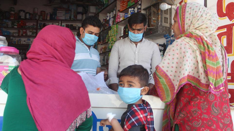 Shopkeepers wearing face masks attend to customers outside the SGT Hospital in Gurugram where a coronavirus quarantine ward has been set up.