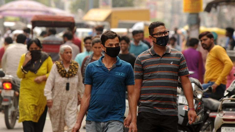 People wearing protective face masks as a precaution against coronavirus, at Sadar Bazar near Sohna chowk, in Gurugram, India, on Friday, March 20, 2020.