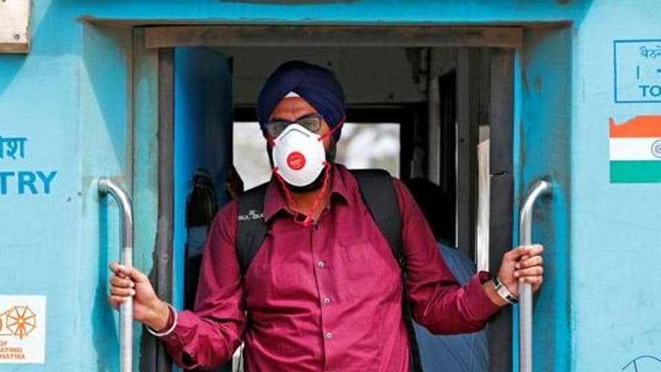 A man wearing a mask as a precaution against the spread of coronavirus stands onboard a train at a railway station in New Delhi.