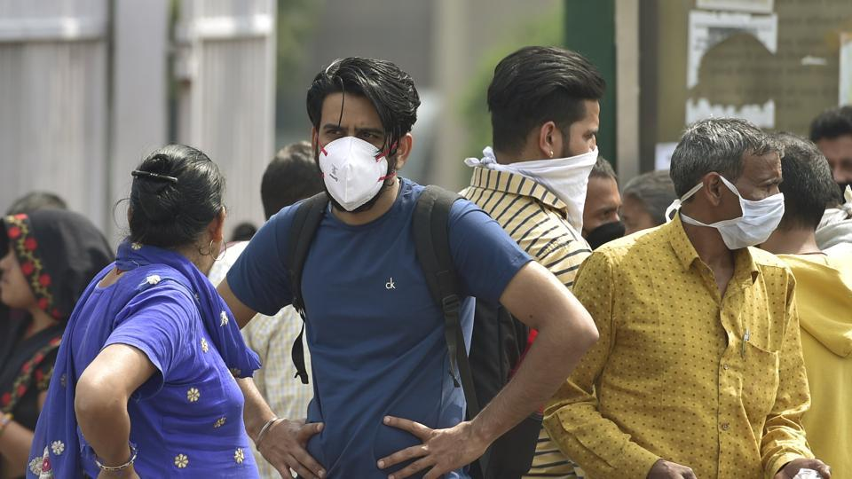 People wear protective masks as precaution against coronavirus, outside AIIMS hospital in New Delhi on March 20.
