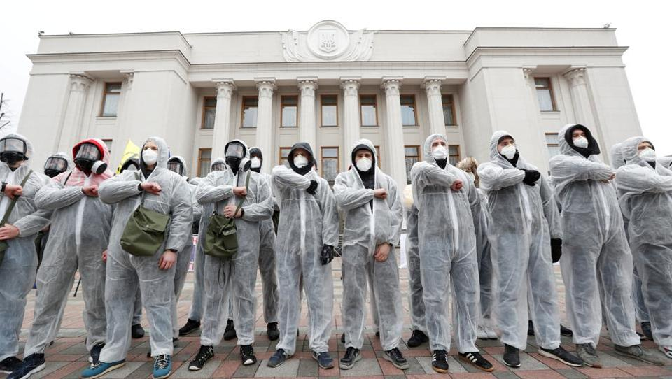 Activists of the National Corps political party are seen wearing protective gear as they take part in a rally demanding to quarantine lawmakers amid coronavirus (COVID-19) concerns, in front of the Ukrainian parliament building in Kiev. (Valentyn Ogirenko / REUTERS)
