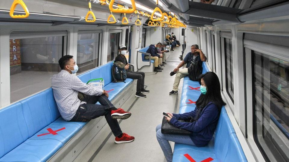People sit on designated areas decided by red cross marks to ensure social distancing inside a light rapid transit train in Palembang, South Sumatra amid COVID-19 outbreak.  (Abdul Qodir / AFP)