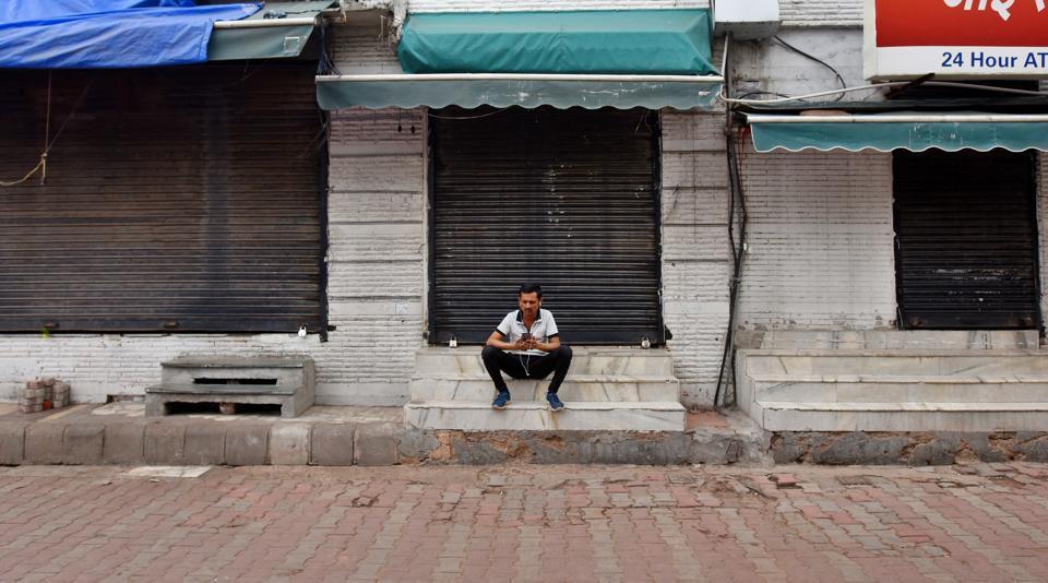 A man sits next to closed shops at Sarojini Nagar market, in New Delhi, India, on Saturday, March 21, 2020.