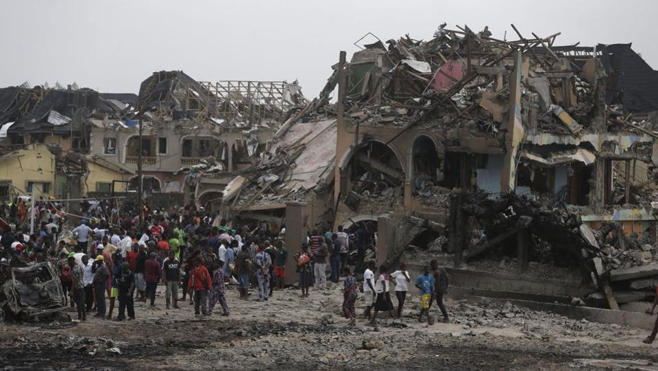 People gather near the site of an explosion in Lagos. An explosion hit Nigeria's commercial capital of Lagos early Sunday, killing more than a dozen people. (AP / PTI)