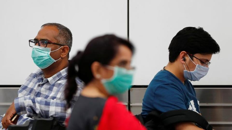 Coronavirus: Passengers wearing protective masks sit at an airport terminal following an outbreak of the coronavirus disease (COVID-19).
