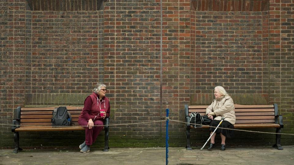 Two women observe social distancing measures as they speak to each other from adjacent park benches amid the novel coronavirus COVID-19 pandemic, in the centre of York, northern England. (Oli Scarff / AFP)