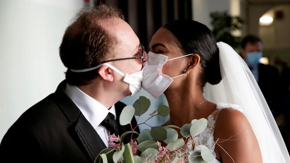 Newlyweds Diego Fernandes and Deni Salgado kiss through protective face masks at a wedding ceremony with only witnesses and no guests, as public gatherings are banned as part of Italy's lockdown measures to prevent the spread of coronavirus disease in Naples, Italy. (Ciro De Luca / REUTERS)