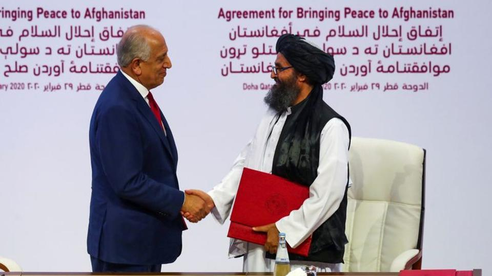 Mullah Abdul Ghani Baradar, the leader of the Taliban delegation, and Zalmay Khalilzad, US envoy for peace in Afghanistan, shake hands after signing an agreement at a ceremony between members of Afghanistan's Taliban and the US in Doha, Qatar.