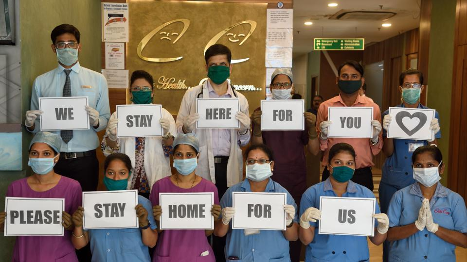 Doctors and supporting staff of a hospital in Mumbai give message to stay indoors, following the call of Janta Curfew given by Prime Minister Narendra Modi .