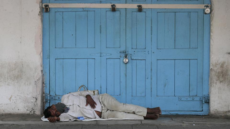 An Indian man rests in front of closed shops during a day long people's curfew as a precautionary measure against COVID-19 in Hyderabad, India, Sunday, March 22, 2020.