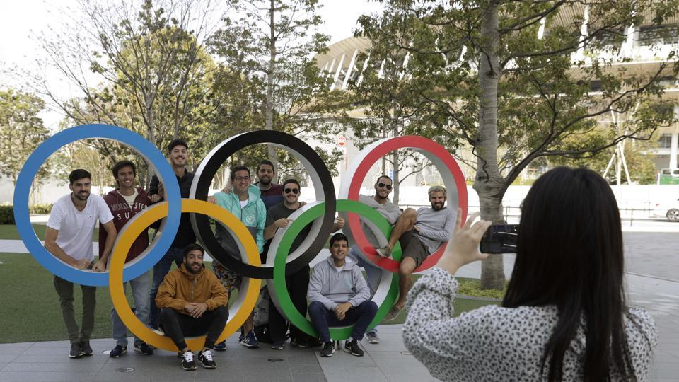 A group of students from Uruguay pose for a souvenir picture on the Olympic Rings set outside the Olympic Stadium in Tokyo.