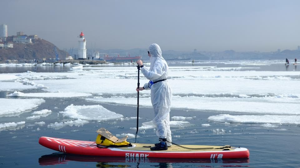 A sup surfer wearing a protective suit as a show of support for the people fighting against the spread of coronavirus disease (COVID-19) takes part at an annual
