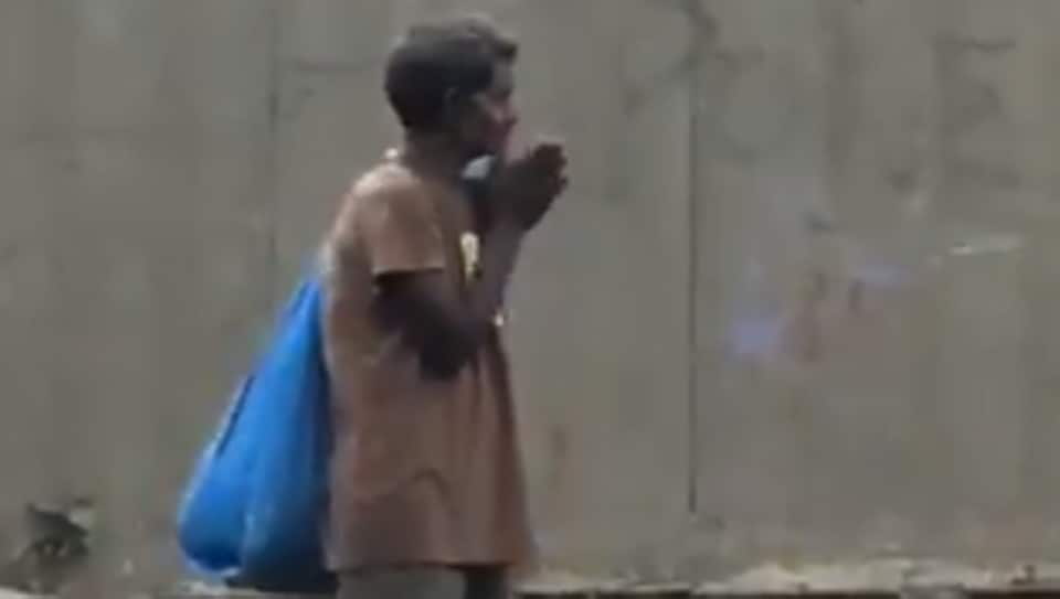The video shows a man with bag standing on the side of the road clapping his hands.