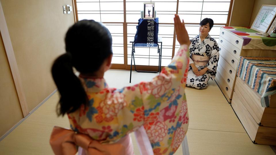 Komaki Yamashita, 49, and her daughter Konoha, 9, receive an online dance lesson by Takujiro Hanayagi, a Japanese traditional dancer, during the novel coronavirus disease (COVID-19) outbreak at their home in Tokyo, Japan. Konoha is staying at home while her school is closed. Although the family sometimes go out to a park, they don't want to travel by public transport so are taking the dance classes online.  (REUTERS / Issei Kato )