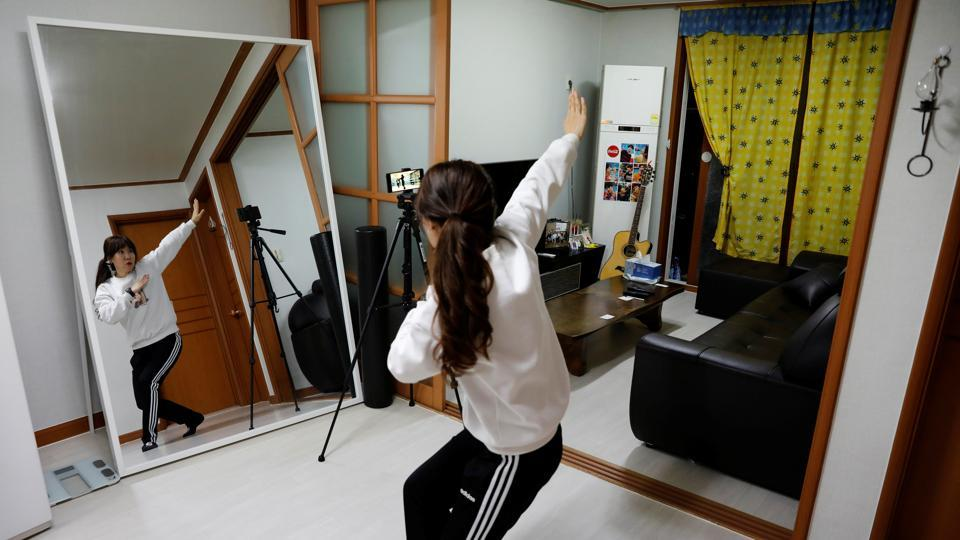 "Kim Myung-hae, 46, a pre-school teacher, practices a dance by the South Korean boyband BTS as she watches a YouTube video at her home, during the novel coronavirus disease (COVID-19) outbreak, in Gumi, Gyeongsang Province, South Korea. Kim has been self-isolating since the end of February. ""Since I can't go outside, I do a lot of online shopping. I surf the internet a lot too... I tend to watch a lot of YouTube,"" Kim said. (REUTERS / Kim Kyung-Hoon )"