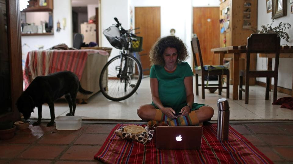 "Ana Pereira, 51, uses her computer to go online and join a virtual picnic with her friends at her home, during the novel coronavirus outbreak, in Caracas, Venuzuela. When asked what she missed most while self isolating she said, ""I want a hug, because you can talk to people but the physical contact is what I miss most."" (Manaure Quintero / REUTERS)"