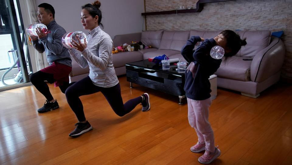 "Dino Lin, Stella Zhang and Wowo Lin, 5, exercise using filled water bottles as weights as they watch a fitness class online at their house, during the outbreak, in Shanghai, China. ""We have been staying at home mostly. We are not forced to do so but believe this is the best way to keep our family away from infection,"" said Dino Lin. (Aly Song / REUTERS)"