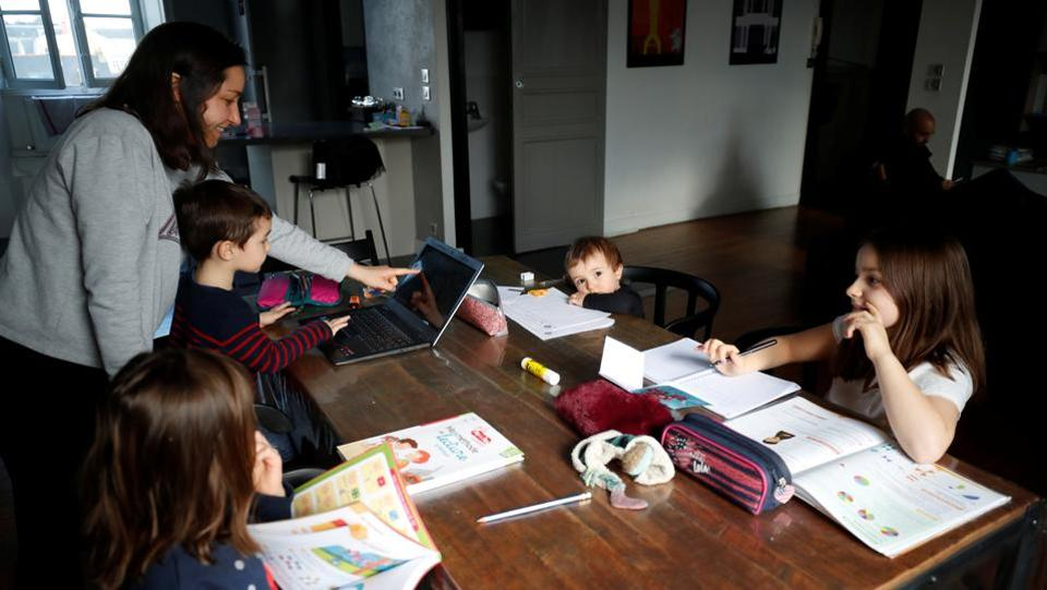 Marina Brebion, a French school teacher, helps her four children with school work,during an imposed lockdown to prevent the spread of the novel coronavirus disease (COVID-19) outbreak, in Nantes, France.