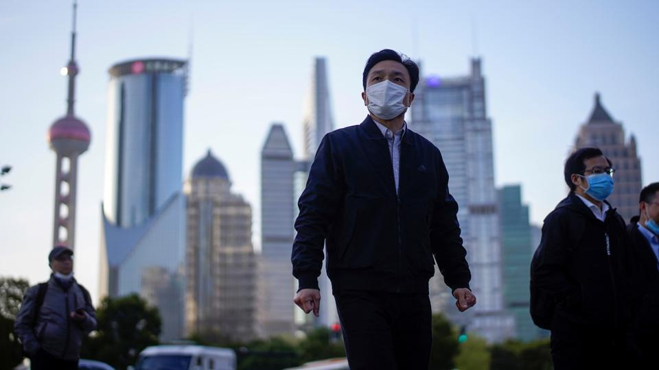 People wear protective face masks, following an outbreak of the novel coronavirus disease (COVID-19), at Lujiazui financial district in Shanghai, China March 19, 2020.