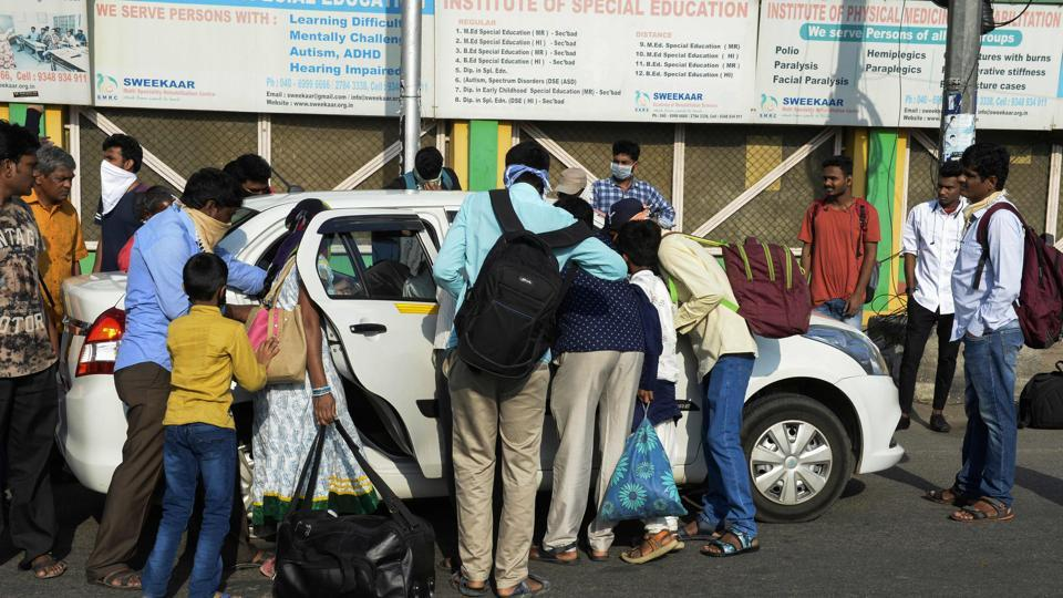 People wearing face masks gather around a private taxi on Monday following Telangana government's order for a complete lockdown till March 31, amid concerns over the spread of the Covid-19.