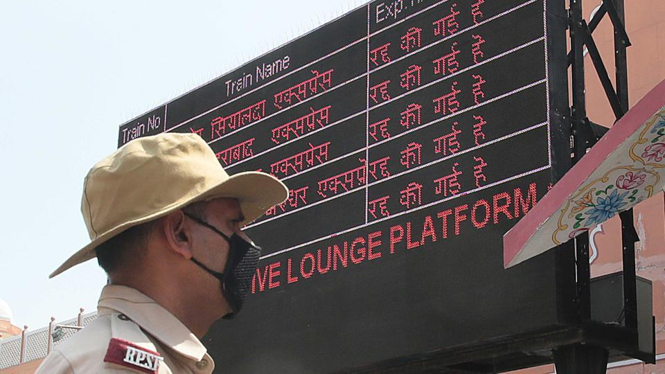 A railway police personnel stands next to a screen showing cancelled trains at Jaipur Railway Station on Sunday, as Rajasthan takes part in Janta Curfew.